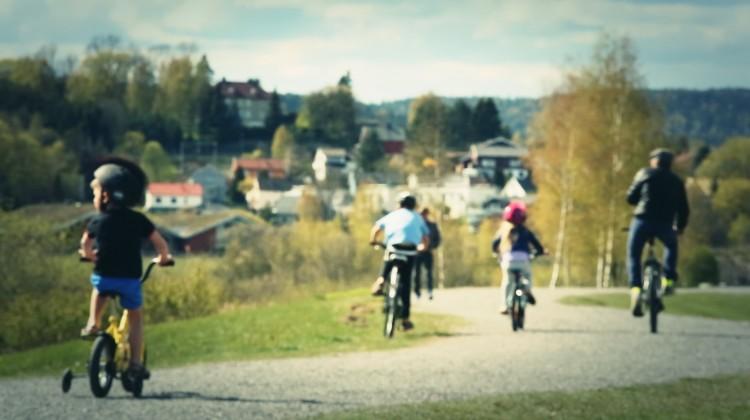 Sykkelfamilie langs flomvollen