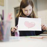 Skolejente som holder opp en tegning av et hjerte